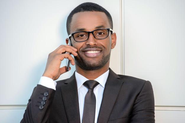 Человек в очках разговаривает по смартфону