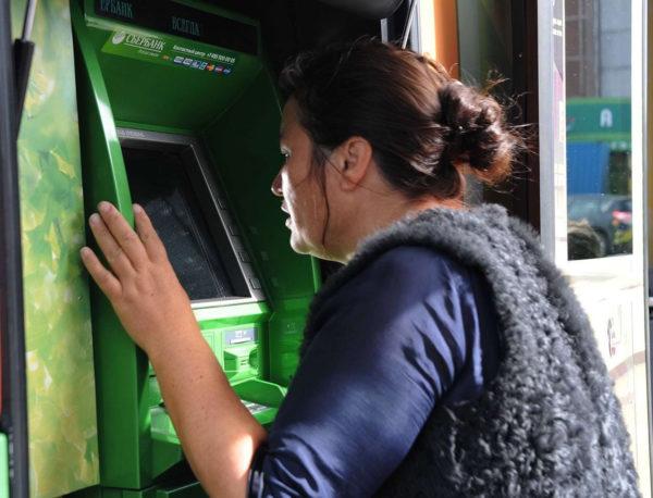 женщина смотрит в банкомат
