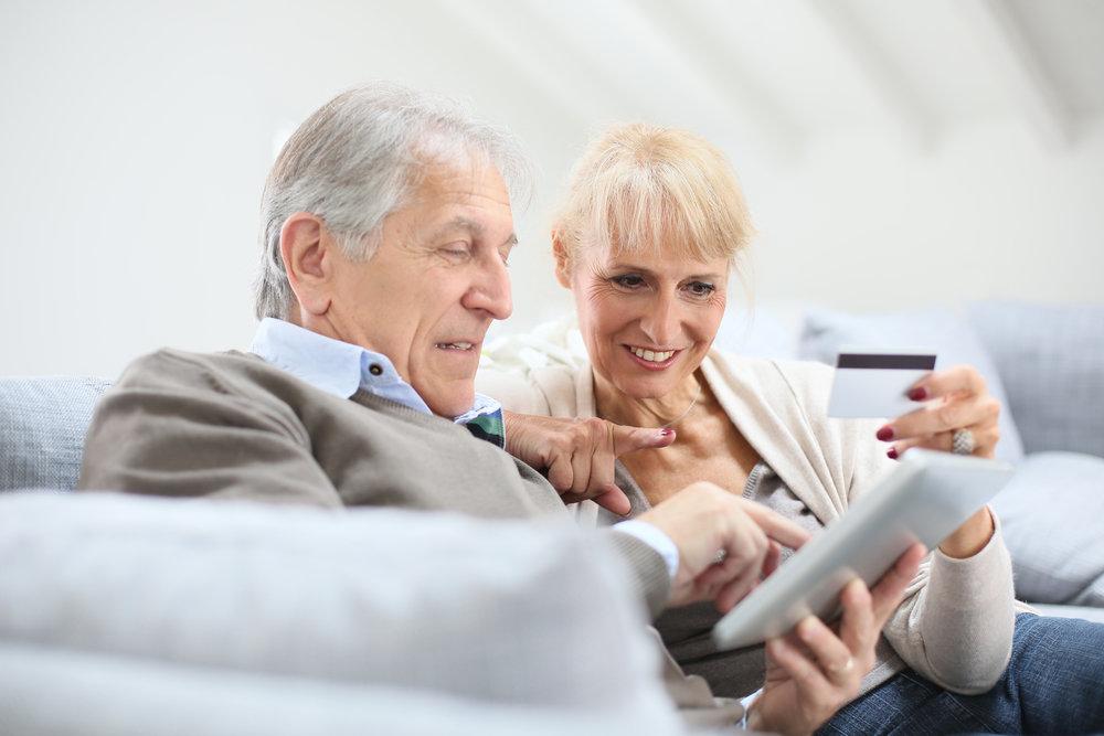 женщина учит старика пользоваться интернет-системой платежей