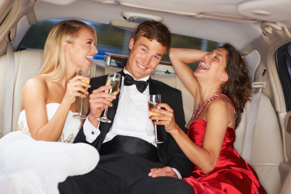 мужчина и две девушки в лимузине с шампанским