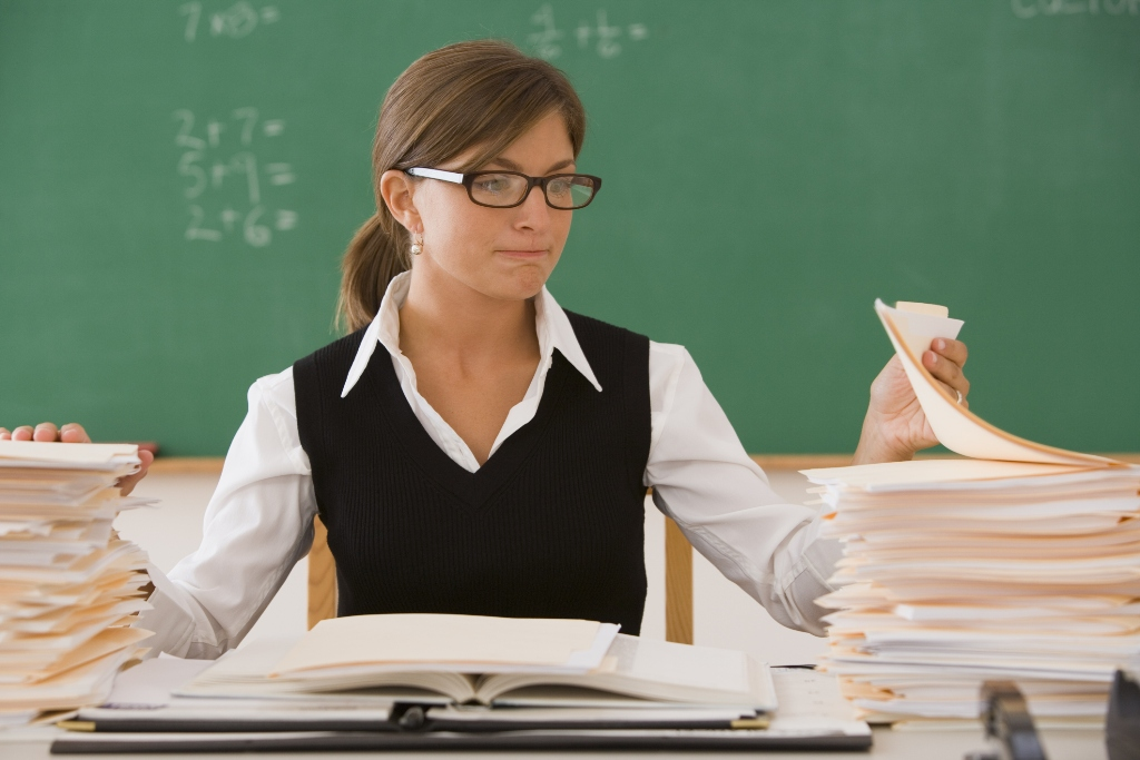 учитель проверяет работы учеников