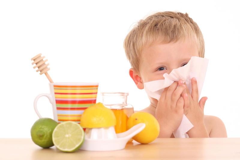 ребенок чихает и смотрит на цитрусовые