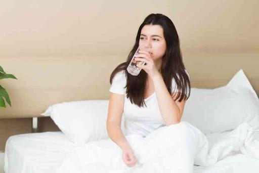 девушка в постели пьет воду
