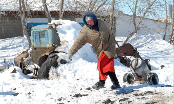 женщина тащит по снегу бетон с водой