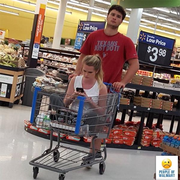 парень катает девушку в тележке в супермаркете