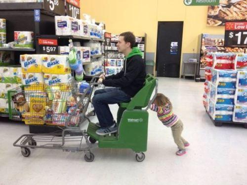 девочка тащит папу на тележке в супермаркете