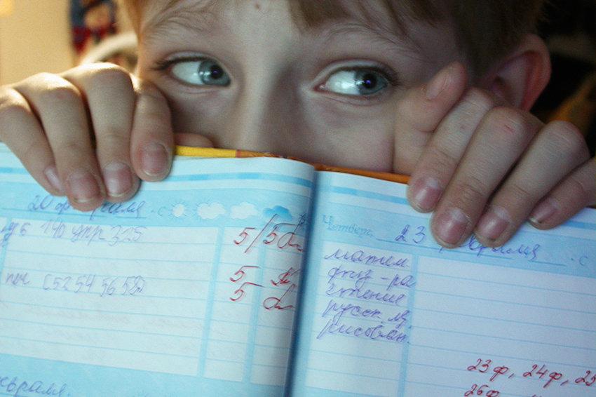 ребенок показывает свой дневник