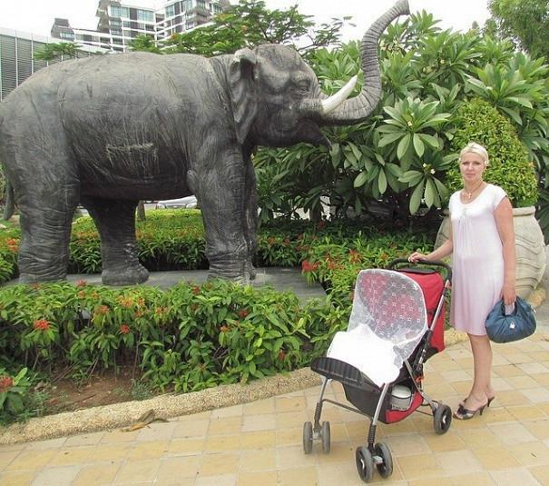 девушка с коляской на фоне статуи слона