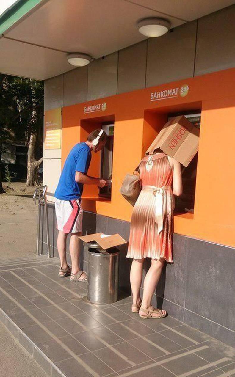 женщина с коробкой на голове у банкомата