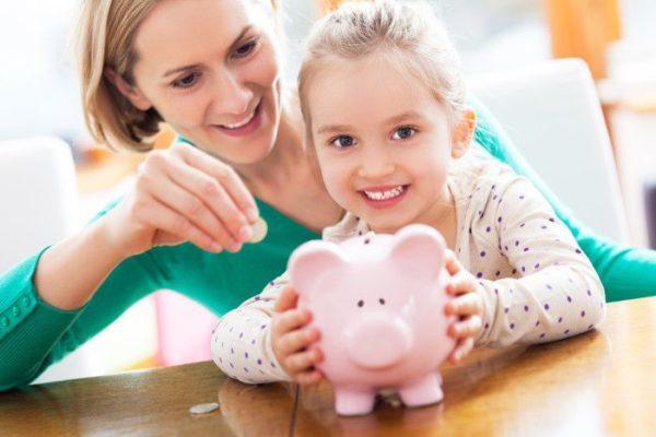 мама с дочерью кладут деньги в копилку