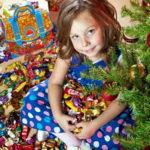 Девочка с конфетами под елкой