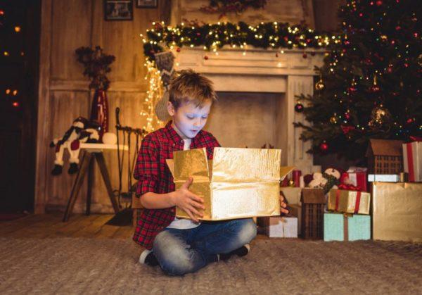 мальчик распаковывает новогодний подарок