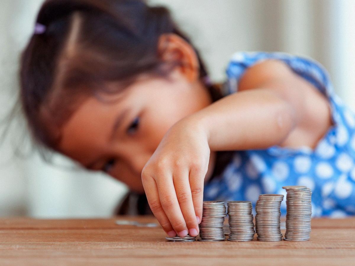ребенок складывает монетки