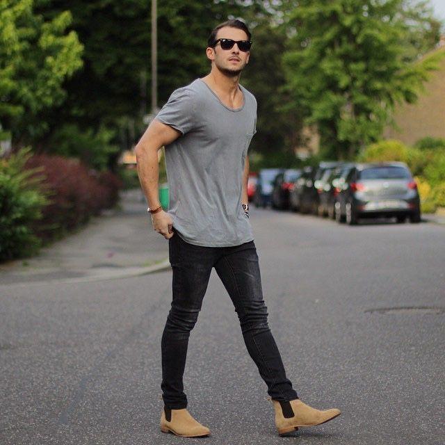 Молодой мужчина в джинсах и в очках идет по улице