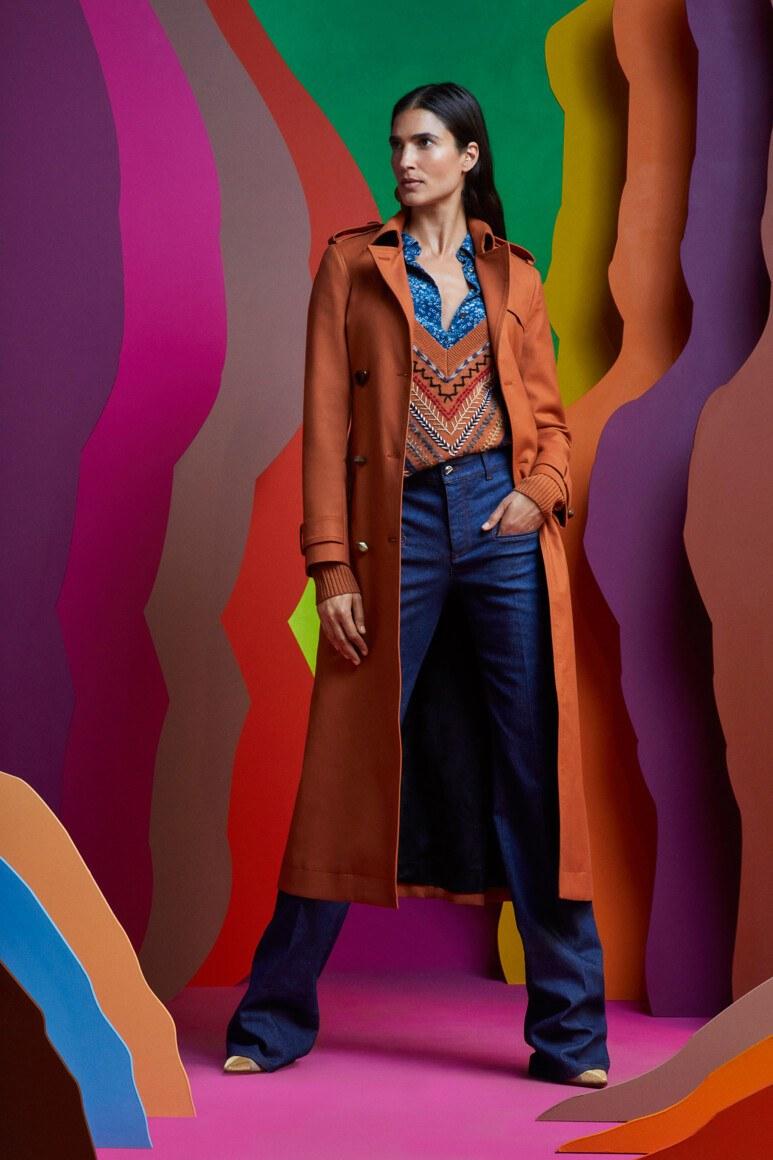 Женщина в тренче и джинсах на фоне ярких декораций