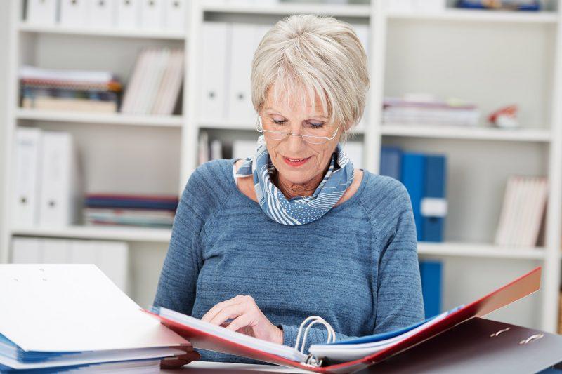 Пожилая дама листает папку с документами