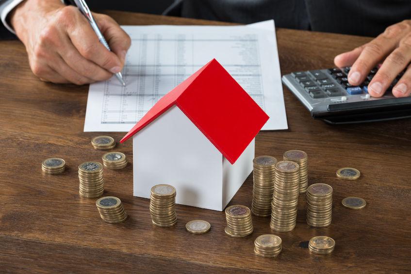Игрушечный домик и стопки монет на столе на фоне рук человека, заполняющего ведомость и считающего на калькуляторе
