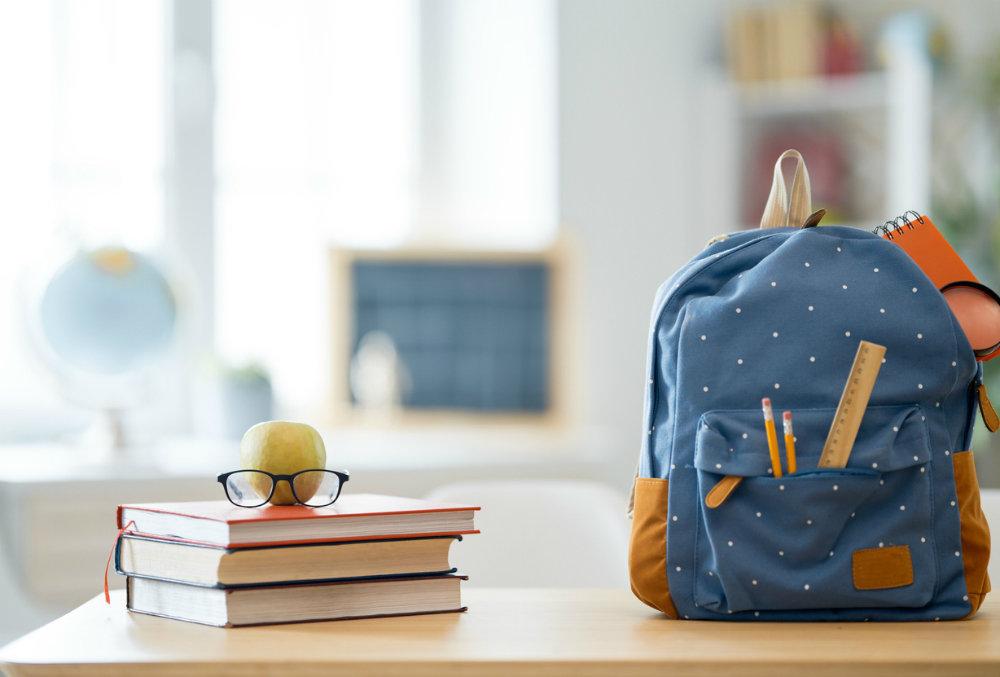 Рюкзак, книги, яблоко и очки на столе