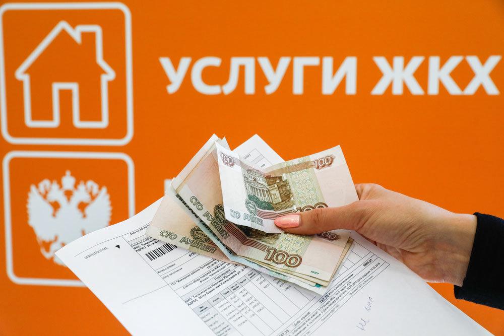"""Квитанция и деньги в женской руке на фоне вывески """"Услуги ЖКХ"""""""