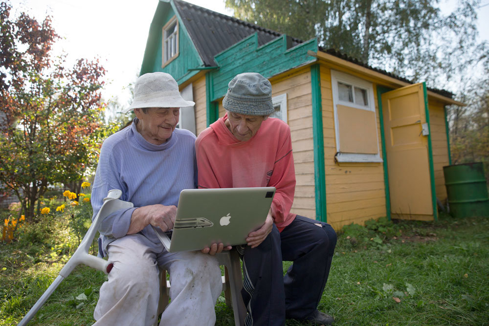 Пожилая пара за ПК на дачном участке