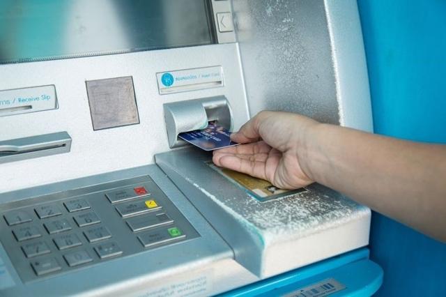 Банкомат и рука с банковской картой