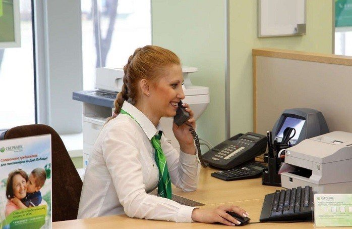Сотрудница банка улыбается разговаривая по телефону