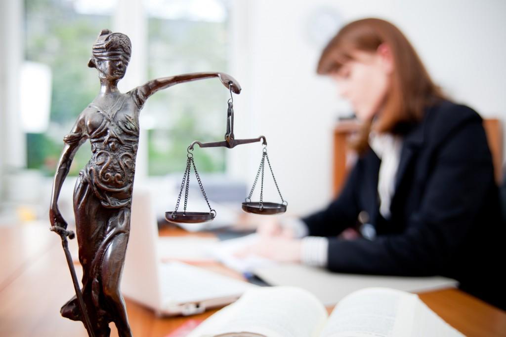 Девушка в костюме сидит за столом со статуэткой Фемиды на переднем плане