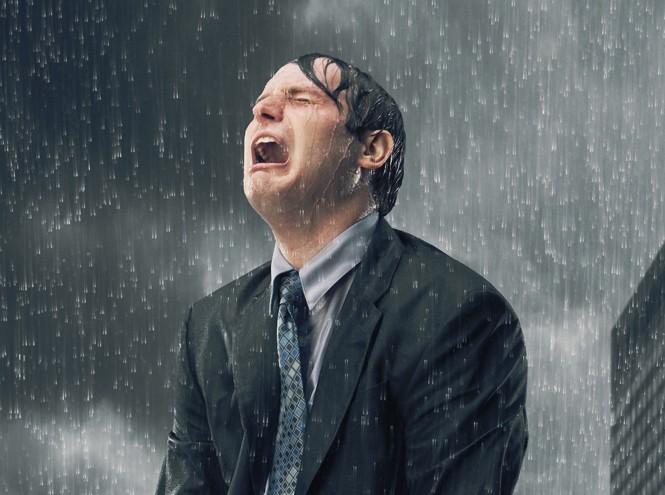 Мужчина плачет под дождем