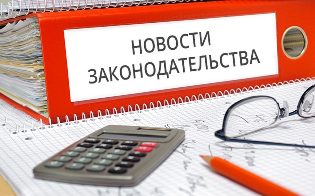 """Папка """"Новости законодательства"""" на столе, калькулятор. очки и карандаш"""