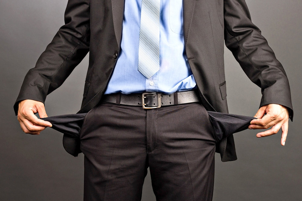 Мужчина в деловом костюме с вывернутыми карманами