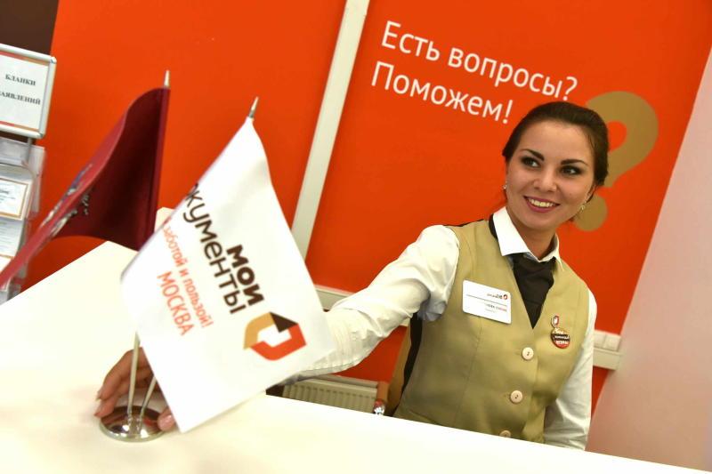Сотрудница МФЦ за стойкой регистрации