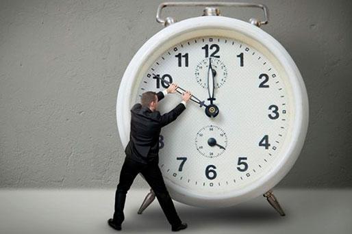 Мужчина в костюме пытается оттянуть назад стрелку часов на гигантском будильнике
