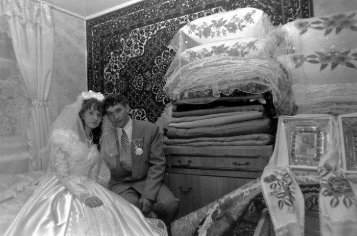 Невеста и жених на кровати, подушки и икона
