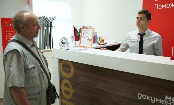Мужчина разговаривает с консультантом на стойке регистрации МФЦ