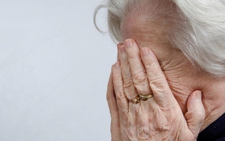 Пожилая женщина плачет, закрывая лицо руками