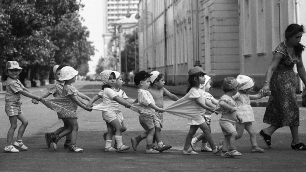 Маленькие дети идут через дорогу