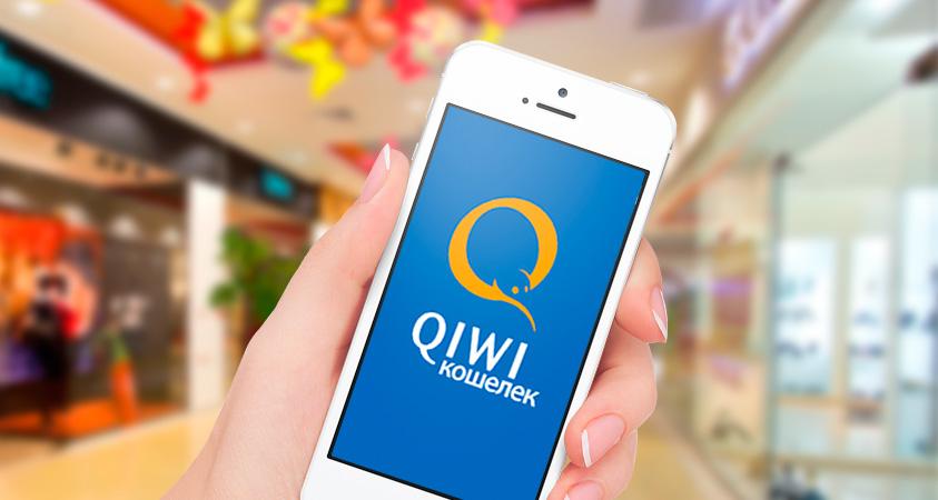 Смартфон в руке с QIwi на экране