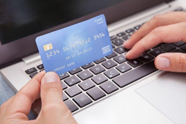 Банковская карта в одной руке и клавиатура ноутбука под другой