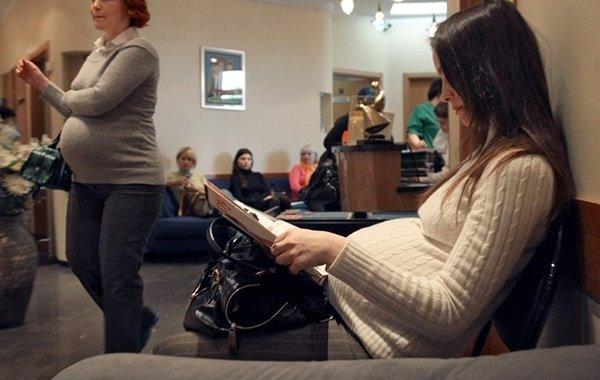 Беременная женщина сидит в очереди