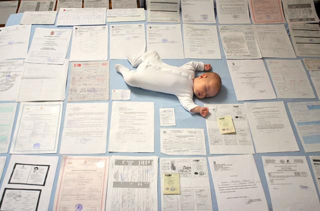 Грудничок в окружении документов и ксерокопий