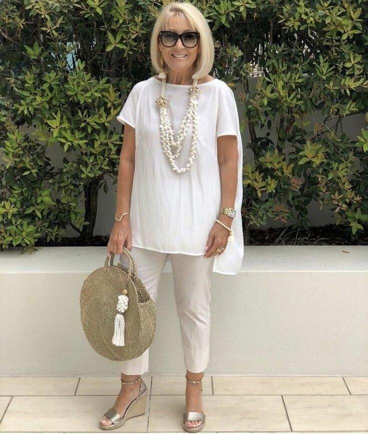 Женщина в белой тунике и бежевых брюках