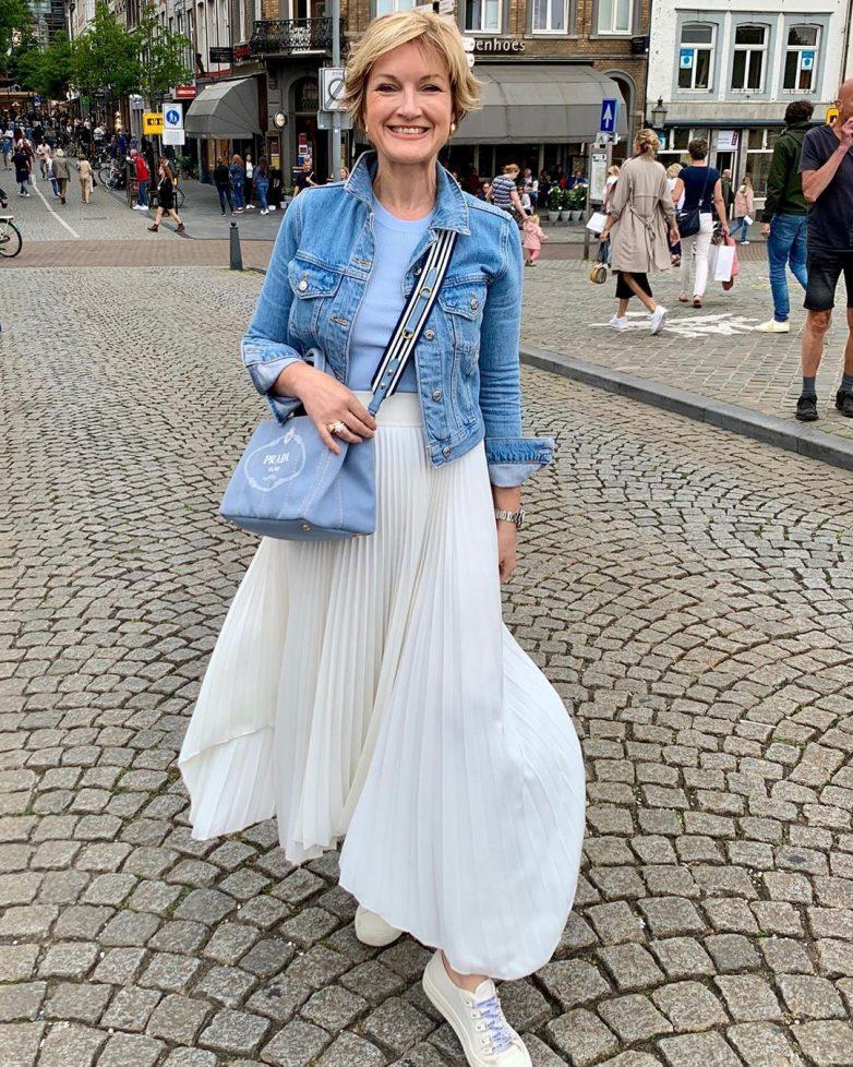 Женщина в джинсовой куртке и белой юбке