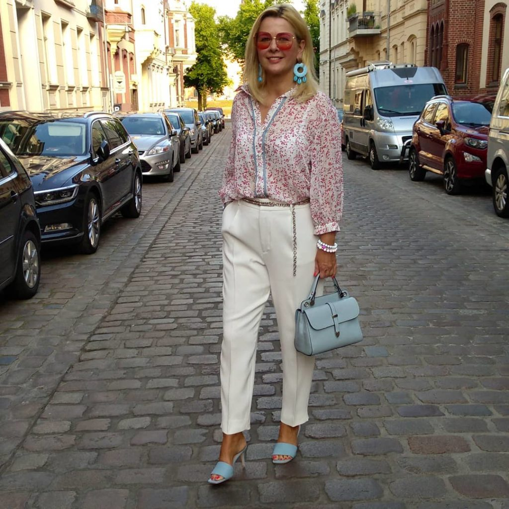 Девушка в цветастой блузе и белых брюках