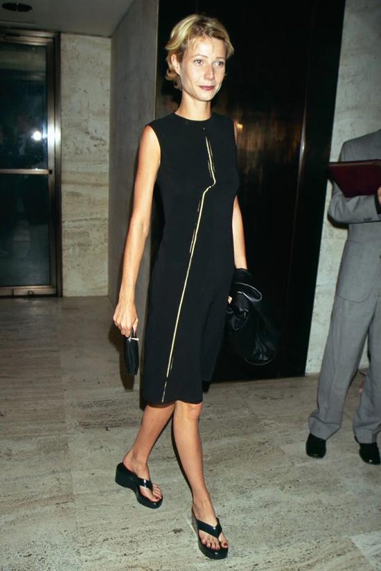 Девушка в черном платье и шлепках