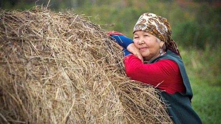 Пожилая женщина возле стога сена