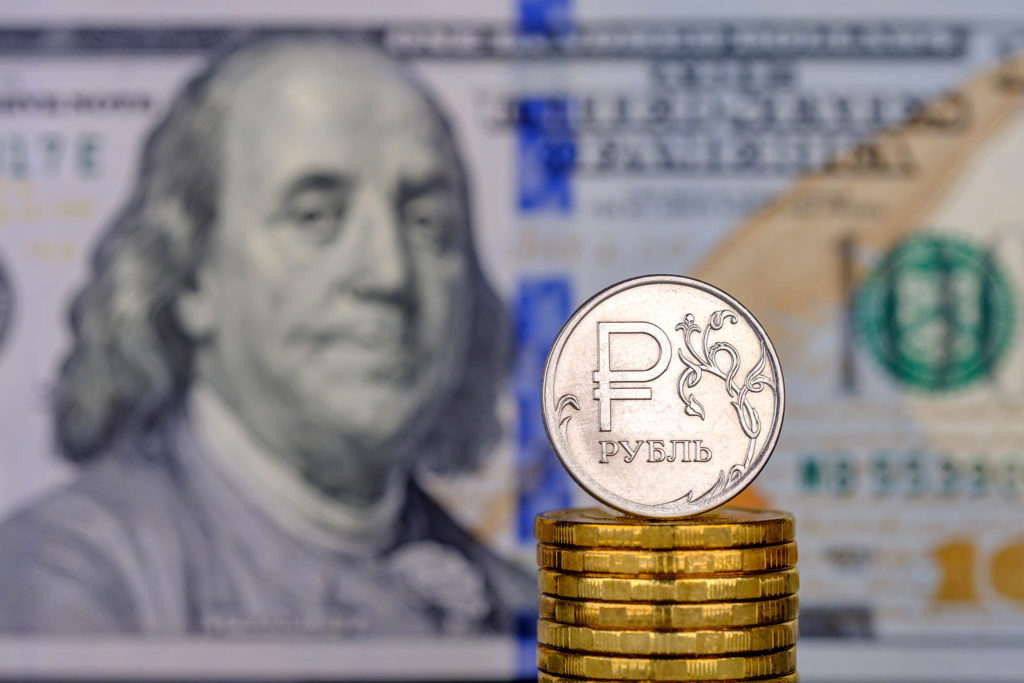Доллар и монеты рублей в стопках