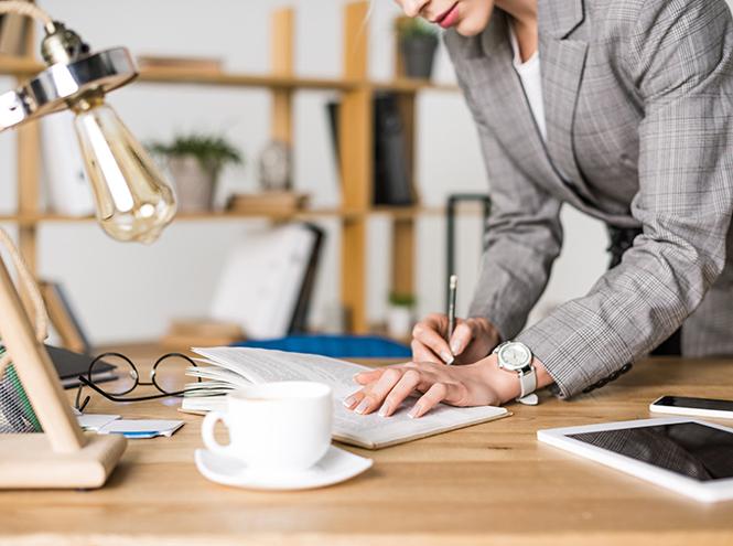 Женщина пишет в блокноте