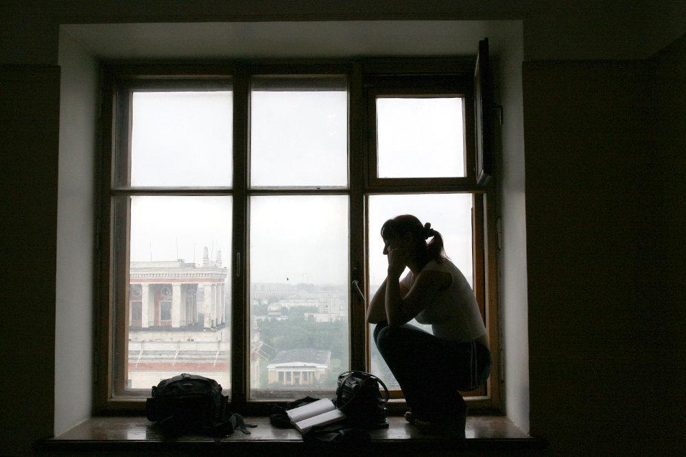 Женщина сидит на окне