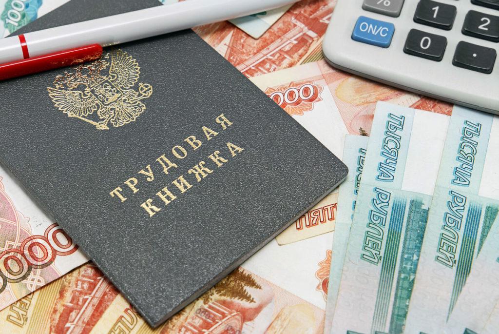 Трудовая книжка, деньги, калькулятор, ручка и документы