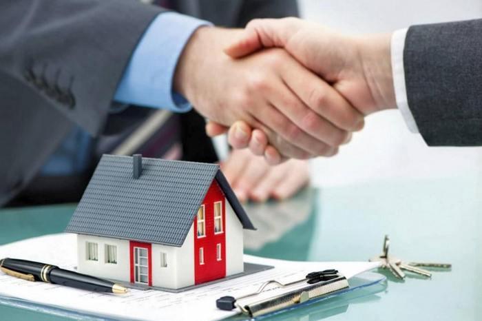 Рукопожатие над игрушечным домиком и подписанным договором с ключами